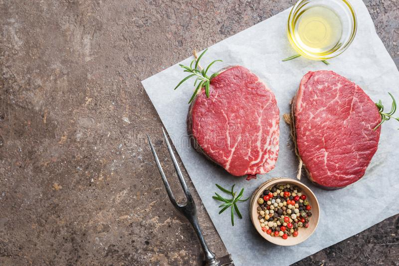 Raw marbled meat steak. Filet Mignon with seasonings over stone background, top view stock images