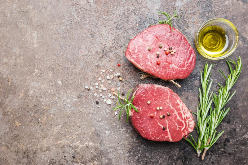 Raw marbled meat steak. Filet Mignon with seasonings over stone background, top view stock image