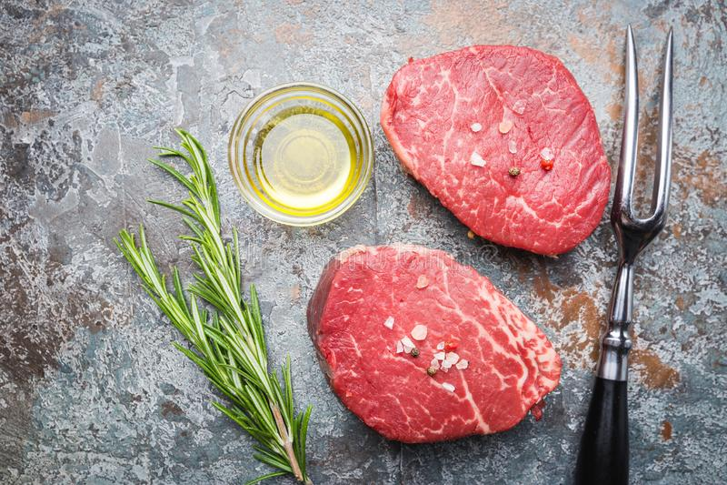 Raw marbled meat steak. Filet Mignon with seasonings over stone background, top view royalty free stock photos