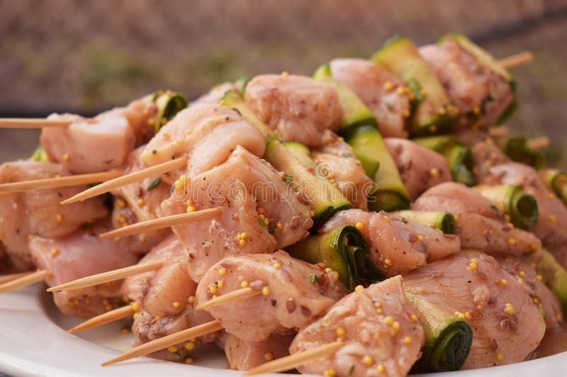 Raw Marinated Chicken Meat Skewers. Barbeque Summer Picnic Food. Grilled Meat over Wooden Background with Spices stock images