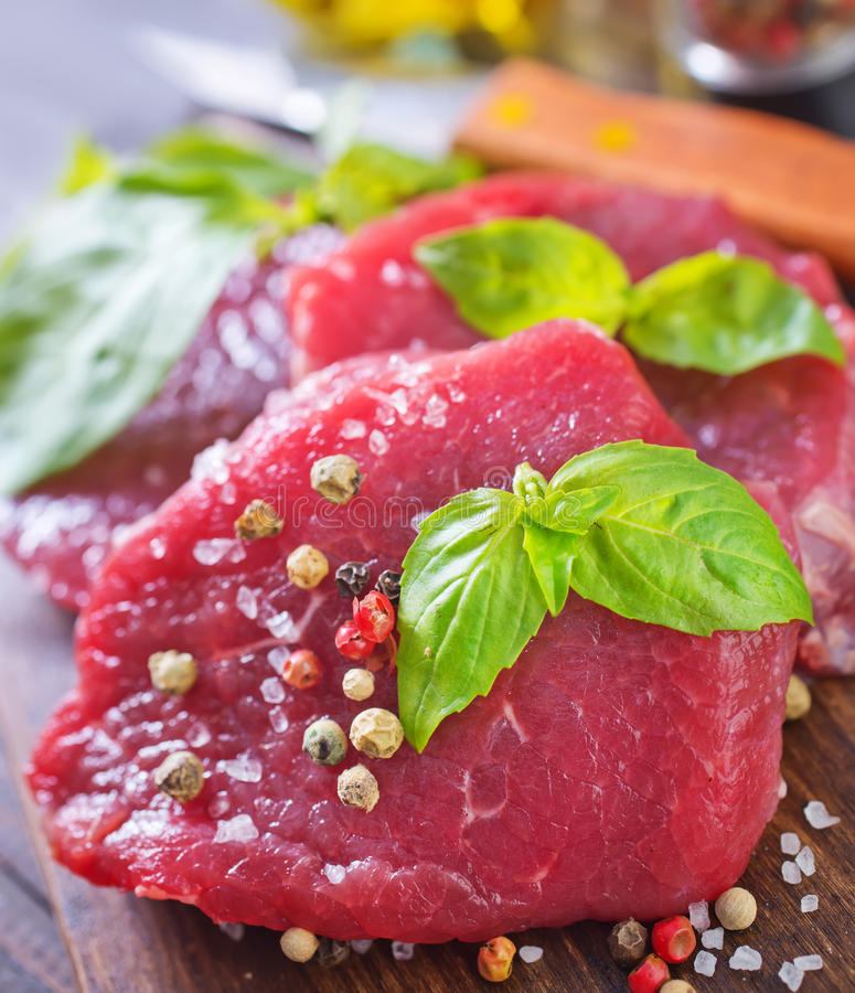 Raw meat. With aroma spice on the board stock photography