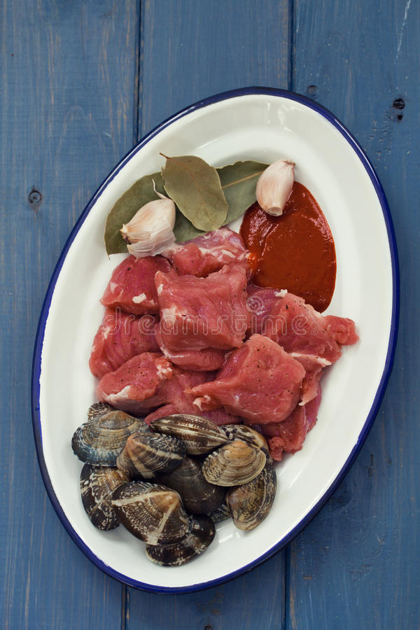 Raw meat with garlic and clams on dish stock photo