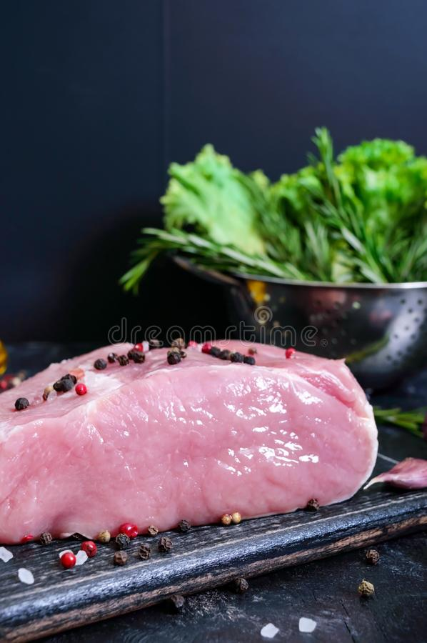 Raw meat. A large piece of pork with spices and salt on a cutting board on a black background.  stock photo