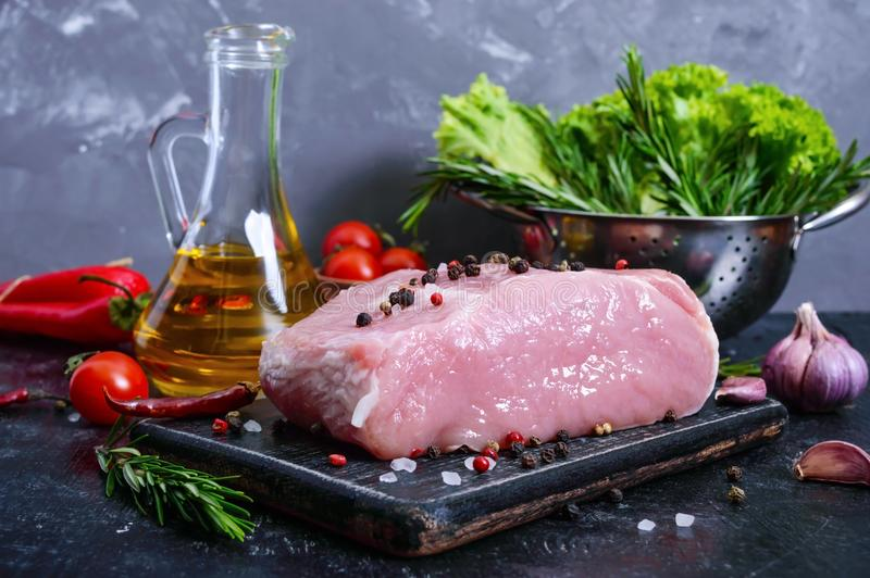 Raw meat. A large piece of pork with spices and salt on a cutting board on a black background.  royalty free stock images