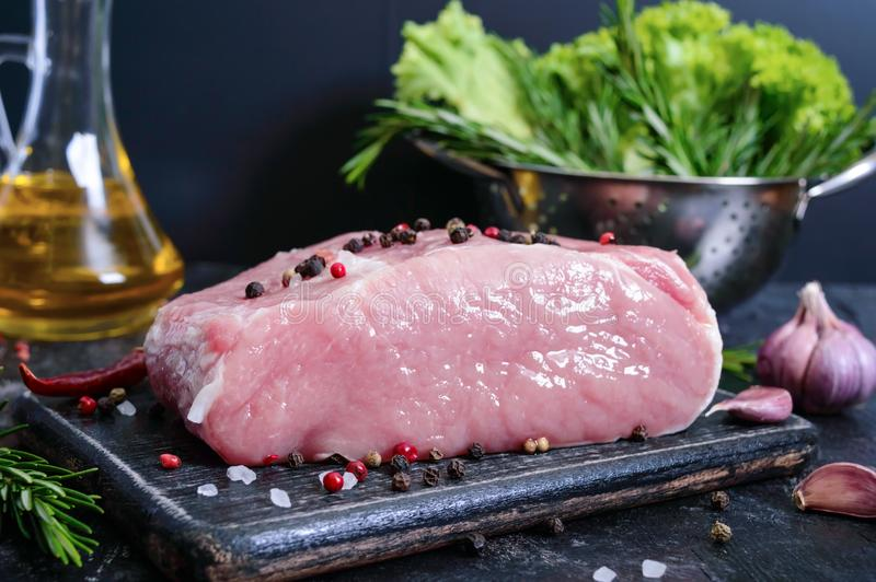 Raw meat. A large piece of pork with spices and salt on a cutting board on a black background.  stock photography