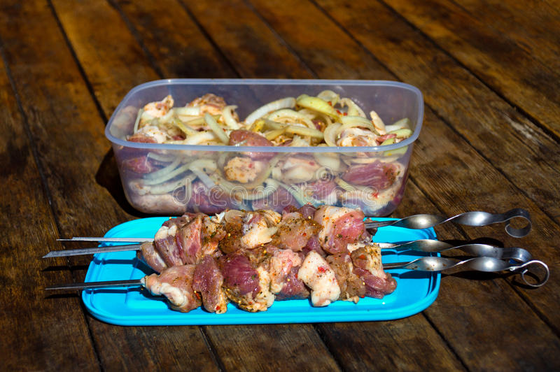 Raw meat, making kebab. Skewers ready for grilling and pieces of pork with onion pepper in container on wooden table stock image