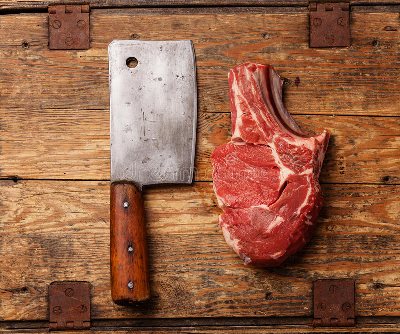 Raw meat and meat cleaver. Raw fresh meat and meat cleaver on wooden background royalty free stock photography
