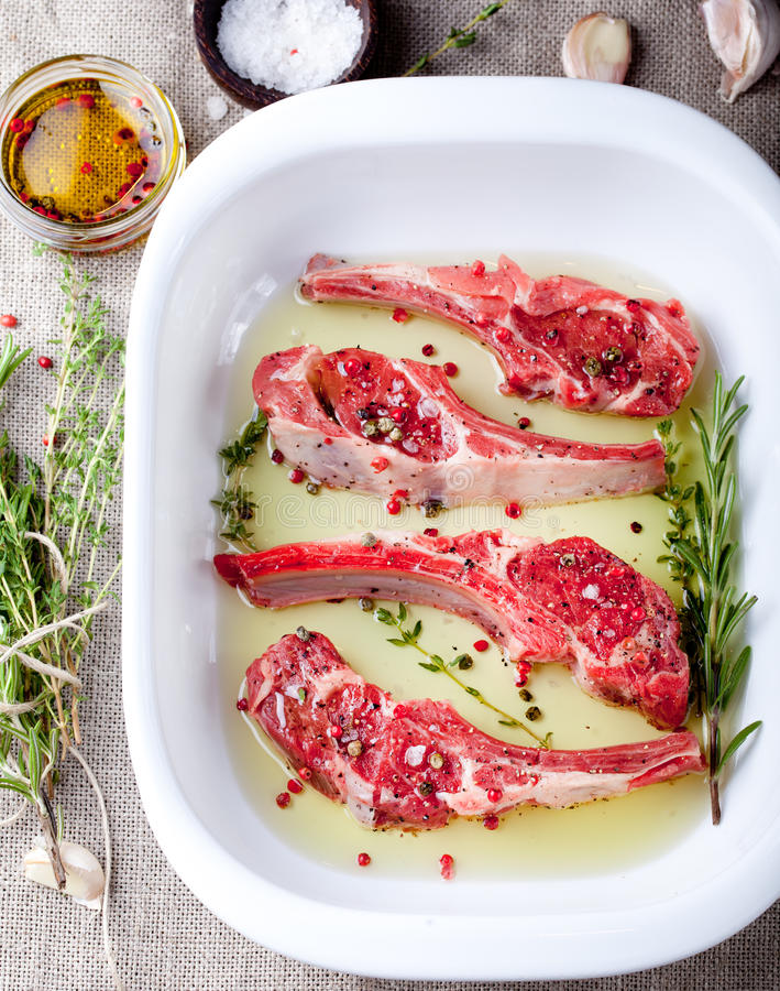 Raw meat, mutton, lamb rack with marinated. Raw meat, mutton, lamb rack with fresh herbs marinated in olive oil with herbs in a ceramic baking dish royalty free stock photography