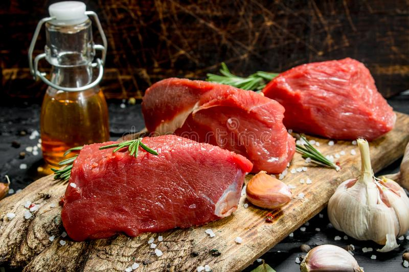 Raw meat. Pieces of fresh beef with spices, garlic and rosemary stock photo