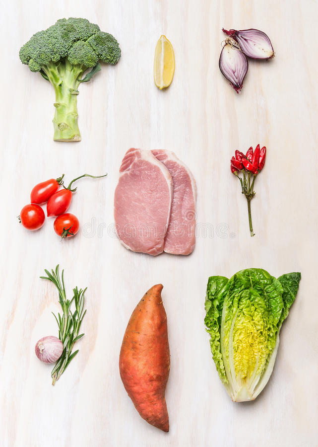 Raw meat pork steak and fresh vegetables ingredients on white wooden background royalty free stock images