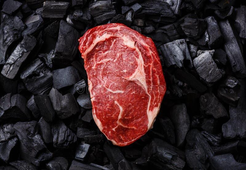 Raw meat Ribeye steak on charcoal. Raw fresh meat Ribeye steak on black charcoal background royalty free stock images
