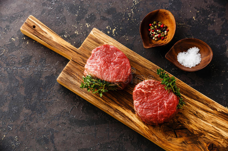 Raw meat Steak filet mignon and seasonings. Raw fresh marbled meat Steak filet mignon and seasonings on black background royalty free stock image
