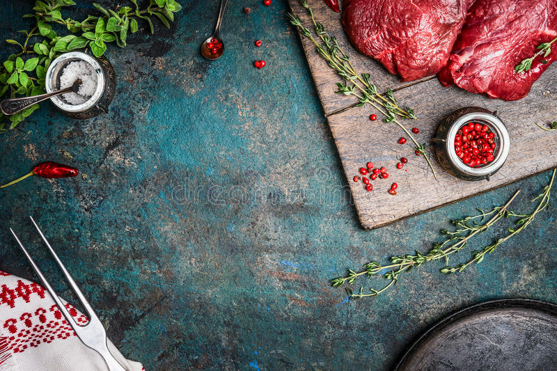 Raw meat steaks with fresh seasonings on rustic wooden background, top view royalty free stock images