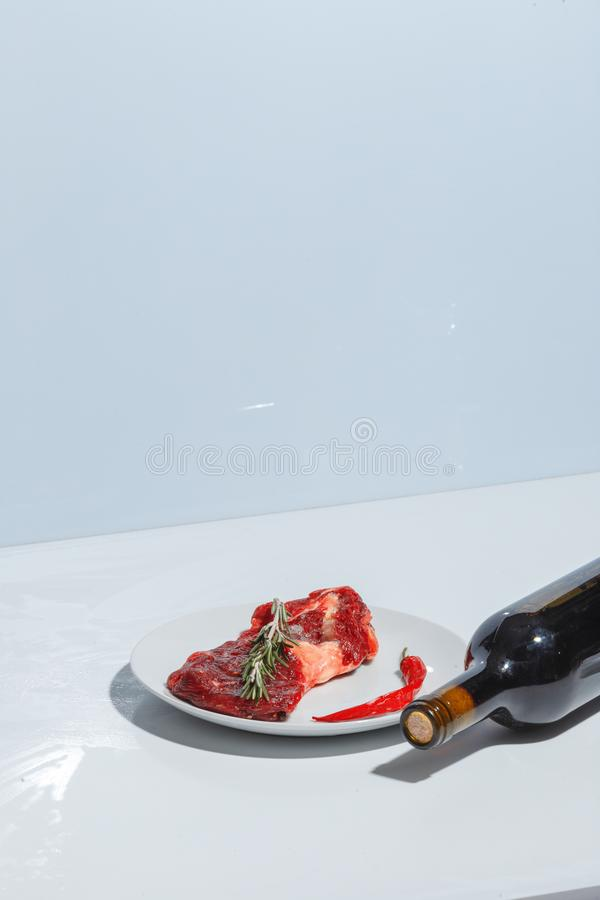 Raw meat on a white plate and a bottle of red wine. Minimalistic creative concept. Food dinner dish cooked herbs gourmet sliced roast beef fat grilled rustic royalty free stock photography