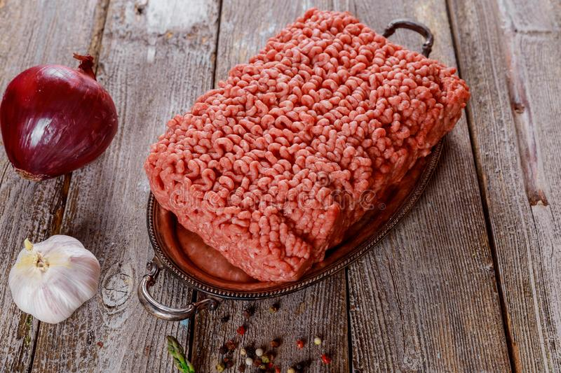 Raw minced meat ingredients on paper with onion, herbs stock photos