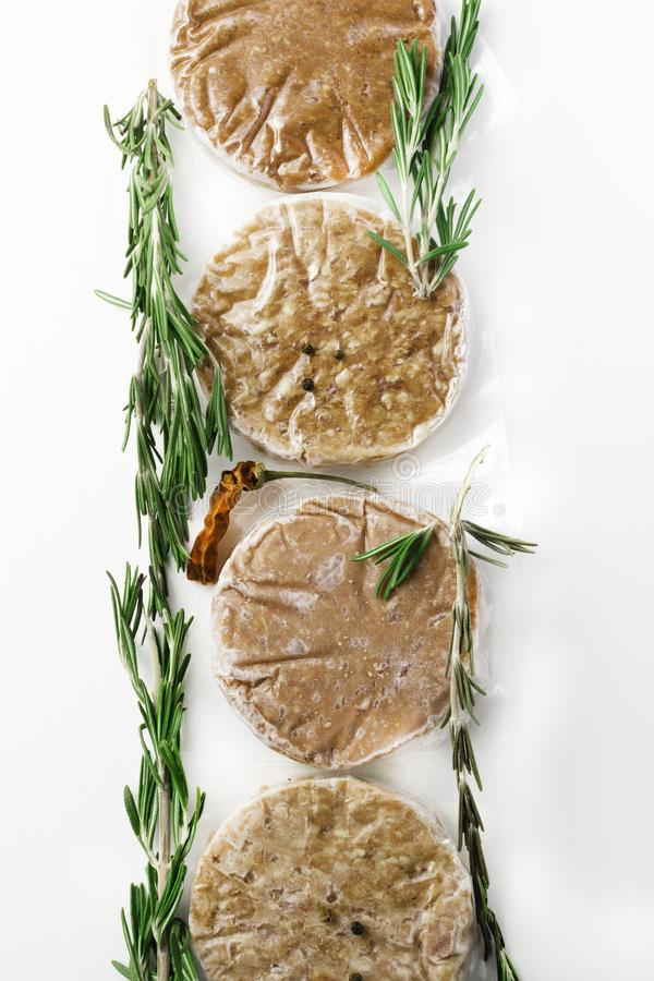 Organic stack of fresh raw burger patty and pepper isolated on white. Raw Minced burger Meat with Herb and Spice Prepared for Grilling with rosemary, hot red royalty free stock images