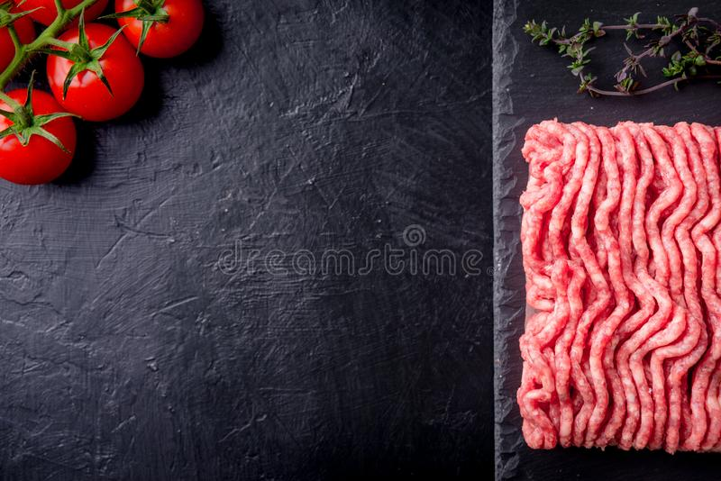 Raw minced meat on slate plate, ingredients for meat with tomato, chili pepper and herbson black background macro top view stock photo