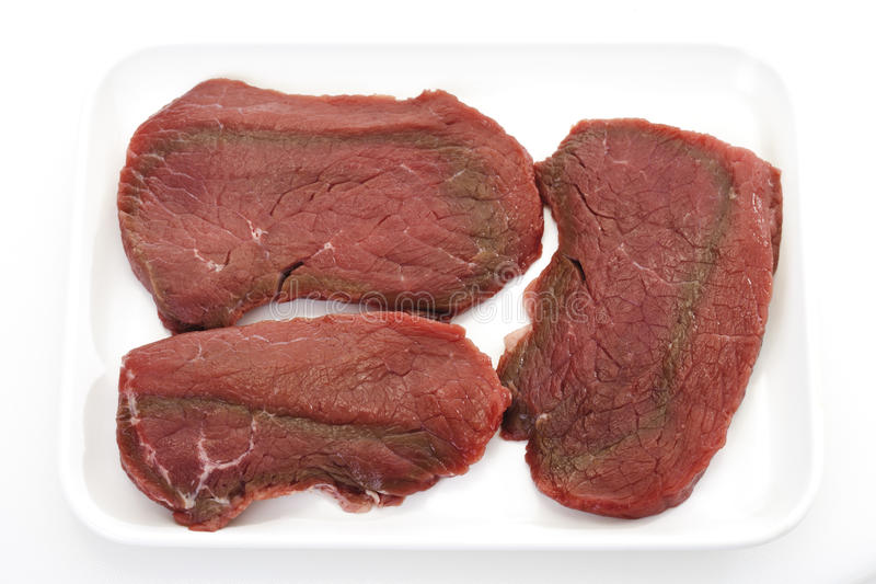 Raw minute steaks on platter stock images