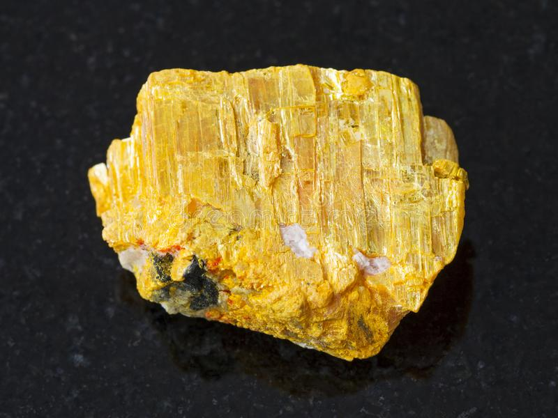 raw native orpiment stone on dark background stock images