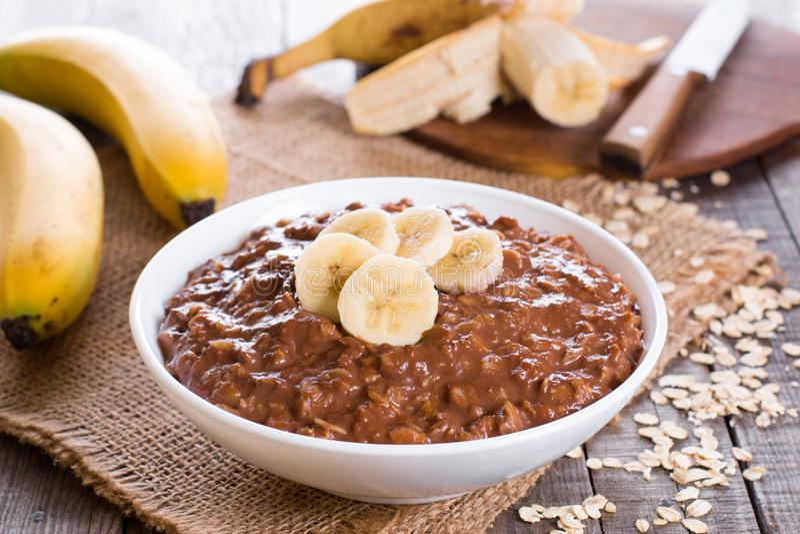 Raw oatmeal porridge with banana and chocolate royalty free stock image