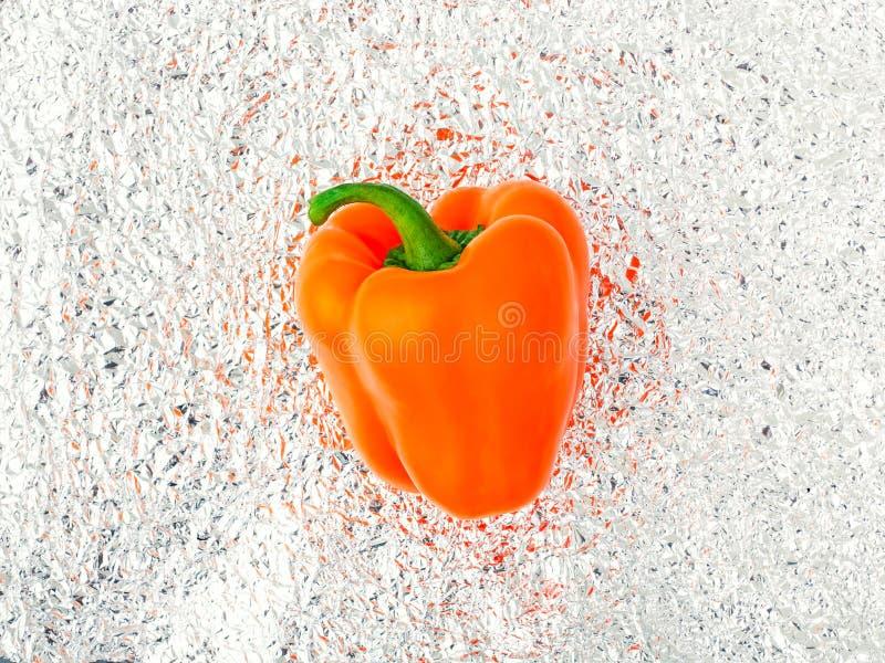 Raw orange pepper on foil. royalty free stock photo