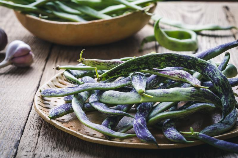 Raw organic rattlesnake beans, plant based food. Raw organic homegrown rattlesnake beans, heirloom vegetables in ceramic plate, plant based food, close up royalty free stock photo