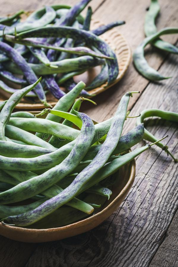 Raw organic rattlesnake beans, plant based food. Raw organic homegrown rattlesnake beans, heirloom vegetables in ceramic plate, plant based food, close up royalty free stock photography