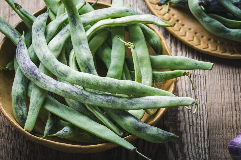 Raw organic rattlesnake beans, plant based food. Raw organic homegrown rattlesnake beans, heirloom vegetables in ceramic plate, plant based food, close up stock image