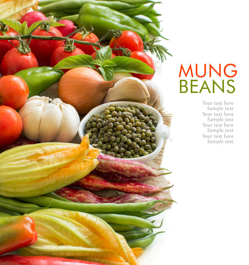Raw organic mung beans in a bowl and vegetables. On white stock photography