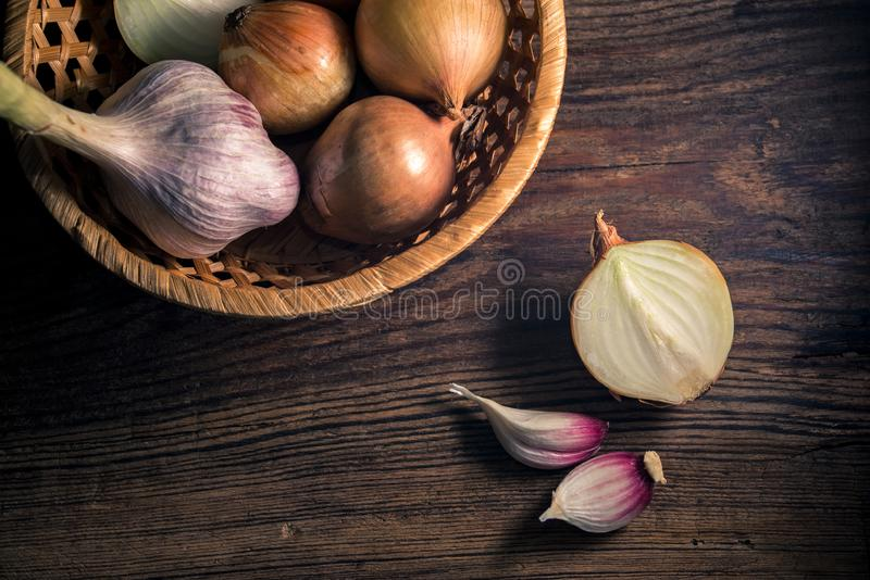 Raw organic onions and garlic on rustic wooden background. Selective focus. royalty free stock photography