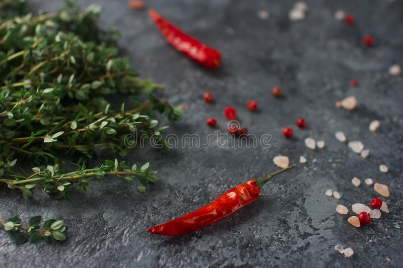 Raw organic spices and herbs, thyme, hot peppers, star anis and himalayan salt. Thyme, hot peppers, star anis and himalayan salt on dark stone background. Raw royalty free stock photography