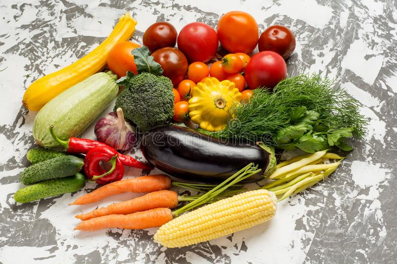 Raw organic vegetables with fresh ingredients for healthily cooking on concrete background, top view, banner. Vegan or stock photos