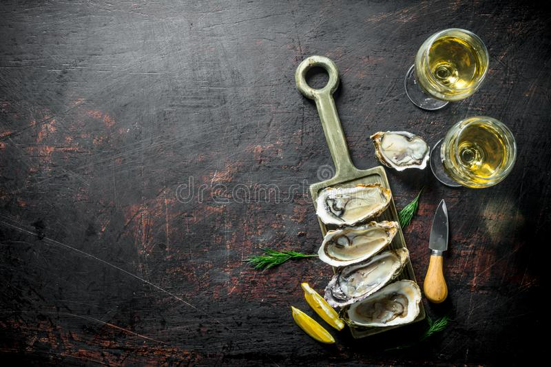 Raw oysters on a cutting Board with two glasses of white wine. On dark rustic background stock images