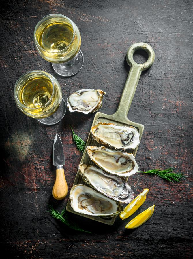 Raw oysters on a cutting Board with two glasses of white wine. On dark rustic background royalty free stock image