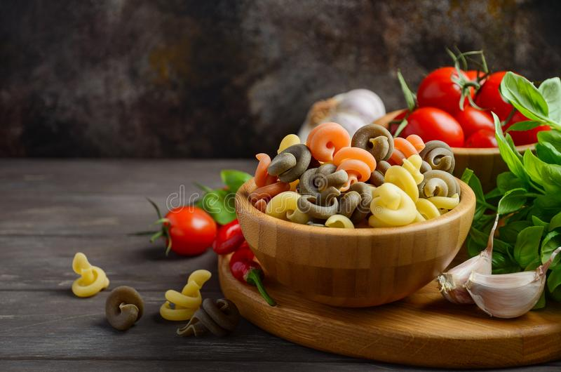 Raw pasta with fresh cherry tomatoes, basil, chili pepper and garlic for Italian food. royalty free stock photos