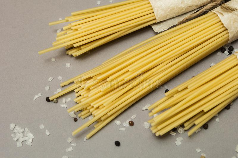Raw pasta on a gray background in a rustic package. Selective focus stock photography