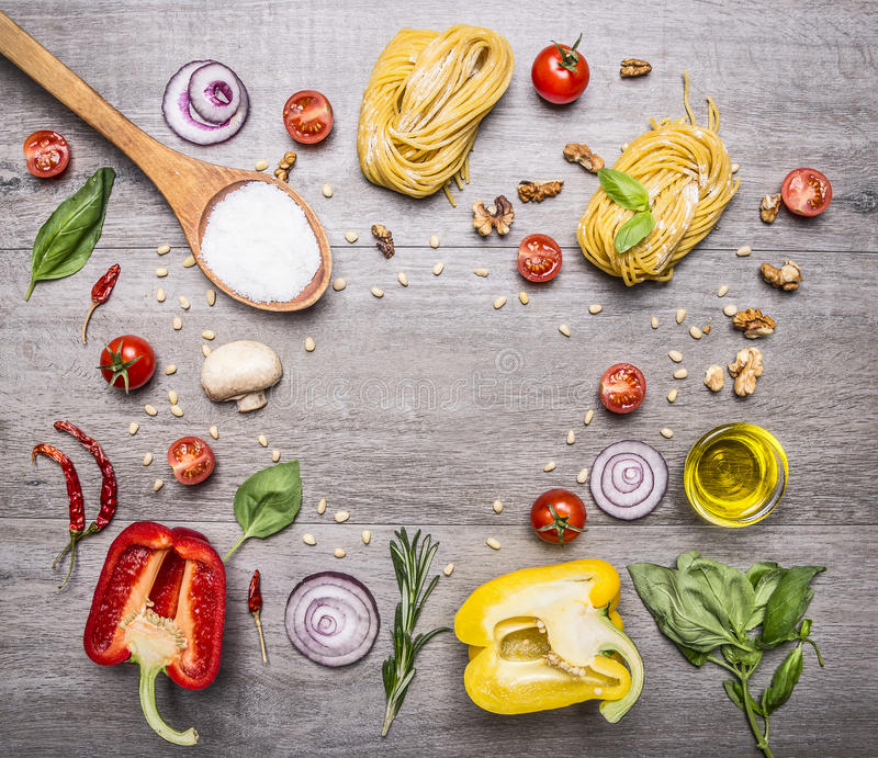 Raw pasta with peppers and cherry tomatoes with a wooden spoon, salt, butter and chives wooden rustic background top view close royalty free stock photo
