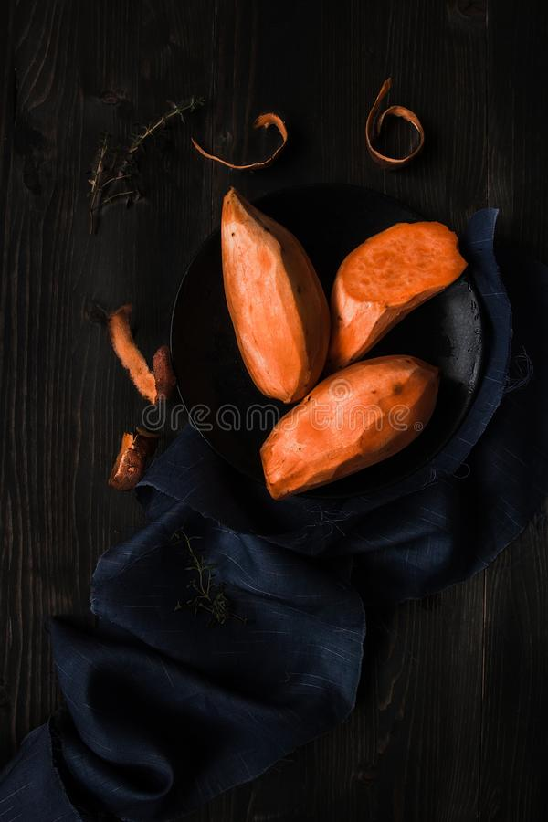 Raw peeled sweet potatoes on the wooden black table top view royalty free stock image