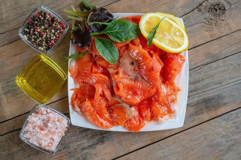 Raw pickled trout fillet and salmon pieces in a white plate. Wooden background. The view from the top. Healthy tasty food stock photo