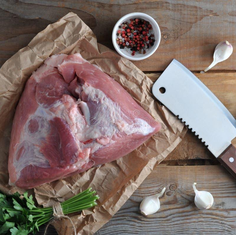 Raw piece of pork big ham and a big chopping knife royalty free stock photo