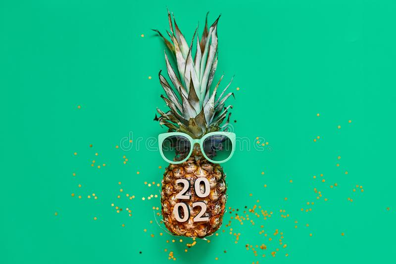 Raw pineapple on green background with golden glitter. Flat lay tropical new year christmas royalty free stock photography
