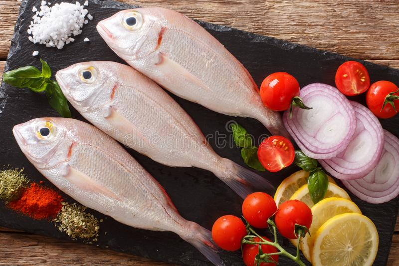 Raw pink dorado or gilt-head sea bream fish with spices, vegetables and lemon close-up on a slate board. horizontal top view. Raw pink dorado or gilt-head sea stock images