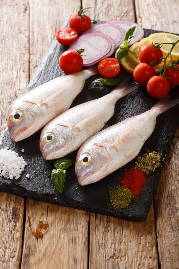 Raw pink dorado or gilt-head sea bream fish with spices, vegetables and lemon close-up on a slate board. vertical. Raw pink dorado or gilt-head sea bream fish stock photos