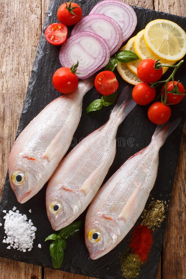 Raw pink dorado or gilt-head sea bream fish with spices, vegetables and lemon close-up on a slate board. Vertical top view. Raw pink dorado or gilt-head sea royalty free stock image