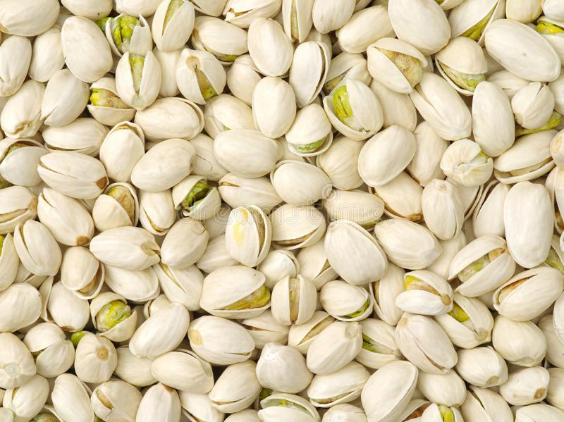 Raw pistachio nuts heap texture. Background stock photos