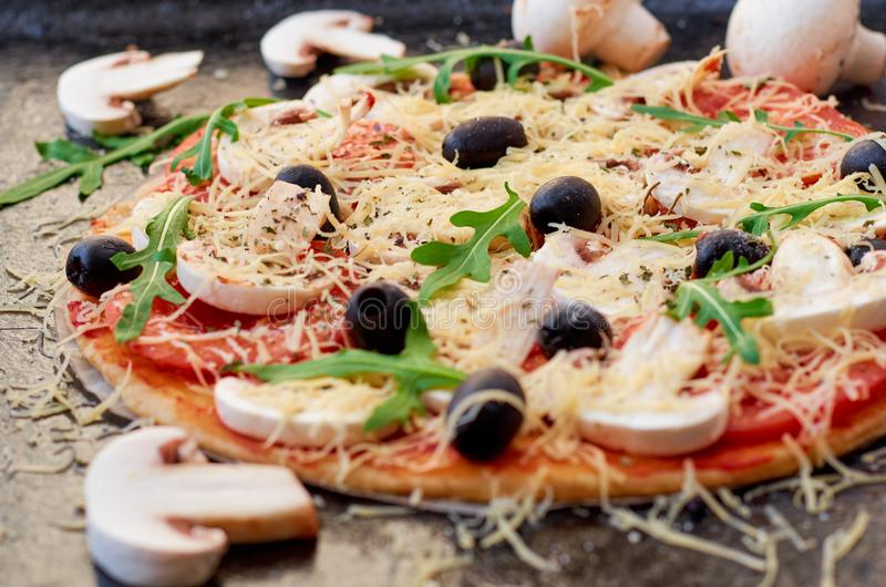 Raw pizza on the black background close up. Vegetarian pizza with cheese, vegetables, mushrooms, black olives and fresh rucola royalty free stock photo