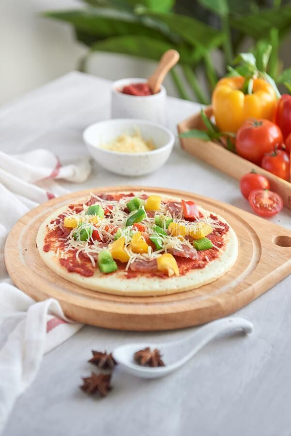 Raw pizza with ingredients in the background.  royalty free stock image