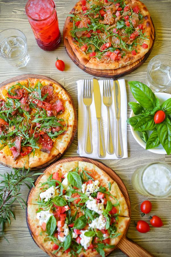 Raw pizza. Rolled out dough on a cutting Board with tomato paste, mozzarella and spinach. On rustic background stock photography