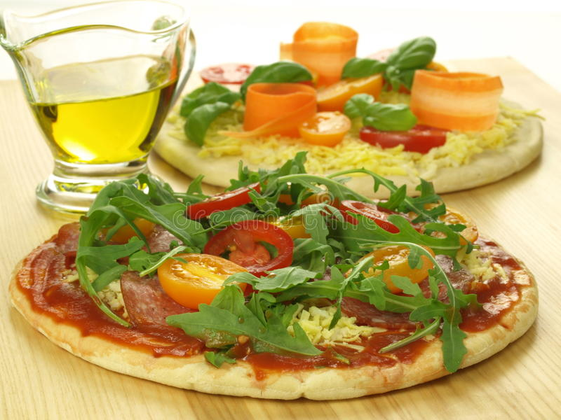 Raw pizzas. Prepared pizzas with vegetables and tomato sauce royalty free stock image