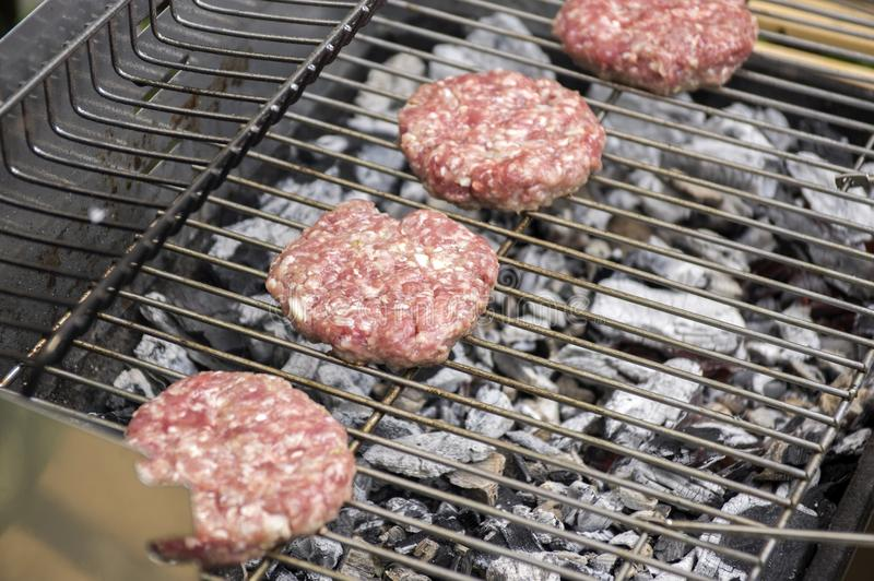 Raw pork and beef meat prepared for hamburgers on barbecue grill treatment stock photo